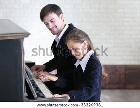 Musician teacher trains to play piano little girl - stock photo