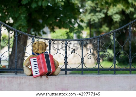Musician teddy bear plays accordions in the street - stock photo