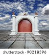 Musician trumpeter blowing its horn to welcome guest at a vintage palace gate with solid timber rustic doors with brass studs against a blue cloudy sky. - stock photo
