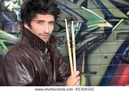 musician with drumsticks against graffiti wall - stock photo