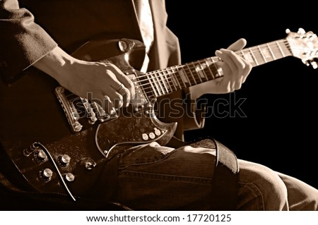 musician with guitar isolated on black background - stock photo
