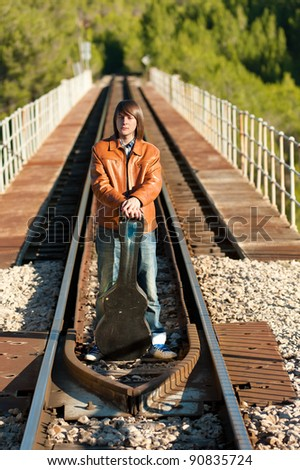 Musician with his guitar on top of a railway bridge - stock photo