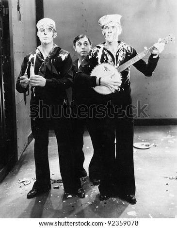 Musicians in a sailors outfit covered with pie - stock photo