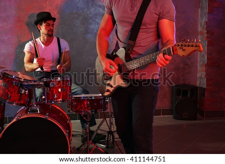 Musicians playing musical instruments and singing songs in a studio - stock photo
