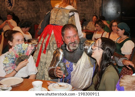 MUSKOGEE, OK - MAY 24: A knight greets female guests during the Queen's tea at the Oklahoma 19th annual Renaissance Festival on May 24, 2014 at the Castle of Muskogee in Muskogee, OK.