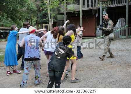 MUSKOGEE, OK - Sept. 12: A herd of bloody zombies surround a runner during the Castle Zombie Run at the Castle of Muskogee in Muskogee, OK on September 12, 2015.   - stock photo