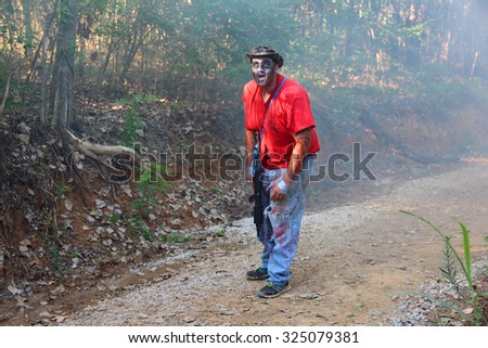 MUSKOGEE, OK - Sept. 12: A man dressed as a zombie waits for runners during the Castle Zombie Run at the Castle of Muskogee in Muskogee, OK on September 12, 2015. - stock photo