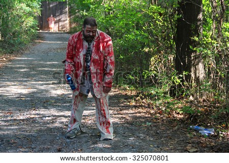 MUSKOGEE, OK - Sept. 12: A man in a bloody jacket waits to scare athletes during the Castle Zombie Run at the Castle of Muskogee in Muskogee, OK on September 12, 2015. - stock photo
