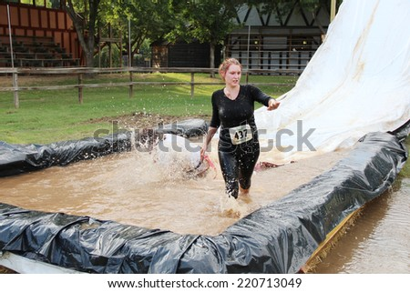 MUSKOGEE, OK - Sept. 13: A woman slides into a muddy pit to avoid zombies during the Castle Zombie Run at the Castle of Muskogee in Muskogee, OK on September 13, 2014.  - stock photo