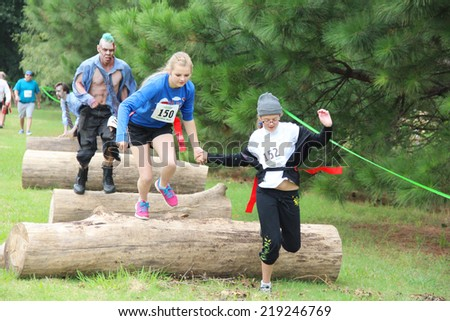 MUSKOGEE, OK - Sept. 13: A young athlete tries to avoid bloody zombies during the Castle Zombie Run at the Castle of Muskogee in Muskogee, OK on September 13, 2014.  - stock photo