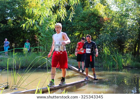 MUSKOGEE, OK - Sept. 12: Athletes go through mud and water to avoid bloody zombies during the Castle Zombie Run at the Castle of Muskogee in Muskogee, OK on September 12, 2015.   - stock photo