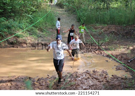 MUSKOGEE, OK - Sept. 13: Athletes run through mud and avoid zombies during the Castle Zombie Run at the Castle of Muskogee in Muskogee, OK on September 13, 2014.  - stock photo