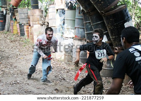 MUSKOGEE, OK - Sept. 13: Athletes run through zombie-infested forest during the Castle Zombie Run at the Castle of Muskogee in Muskogee, OK on September 13, 2014.  - stock photo