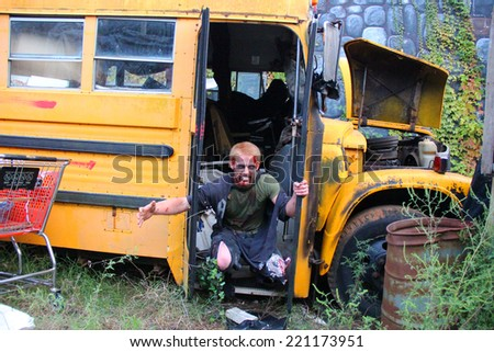 MUSKOGEE, OK - Sept. 13: Bloodied zombie comes out from a school bus during the Castle Zombie Run at the Castle of Muskogee in Muskogee, OK on September 13, 2014.  - stock photo
