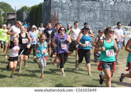 MUSKOGEE, OK - Sept. 14: Runners wearing red life flags overcome obstacles and avoid zombies during the Castle Zombie Run at the Castle of Muskogee in Muskogee, OK on September 14, 2013. - stock photo