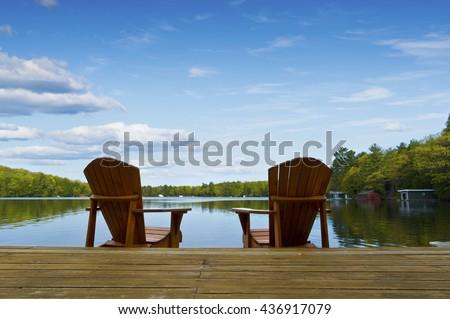 Muskoka chairs facing a calm lake on a wooden dock - stock photo