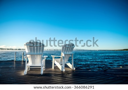 Muskoka chairs on a dock at a blue lake with a blue sunrise and mist coming off the water, closeup - stock photo
