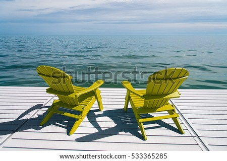 Muskoka Or Adirondack Chairs At The End Of A Pier Overlooking A Large Blue  Lake With