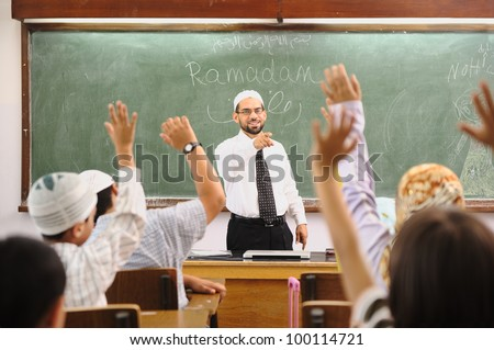 Muslim arabic children with teacher at school - stock photo