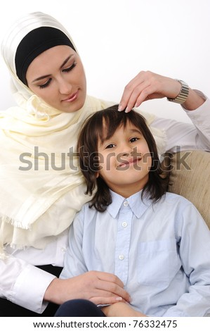 Muslim arabic covered mother and son relaxing at the home - stock photo