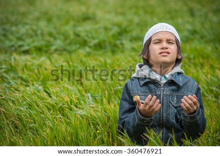 Muslim Arabic kid standing in green beautiful meadow - stock photo