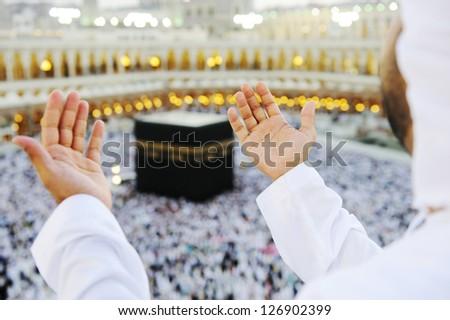 Muslim Arabic man praying at Kaaba in Mecca - stock photo