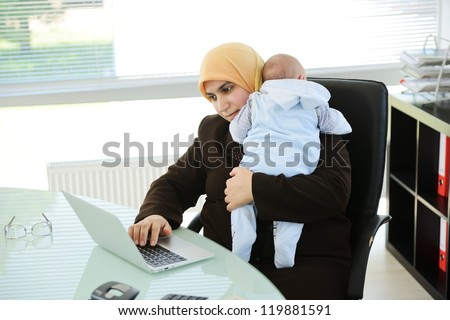Muslim Arabic mother businesswoman with baby at office - stock photo