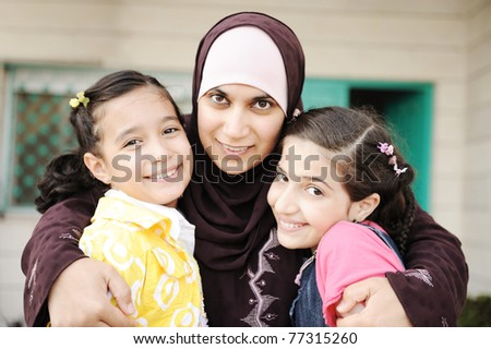 Muslim arabic mother with two daughters, love and care - stock photo