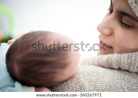 Muslim Arabic woman with newborn baby - stock photo