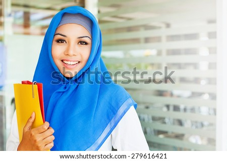muslim asian girl, a college student, holding her workbooks in a class room - stock photo