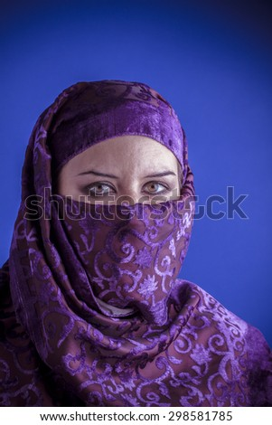 Muslim, Beautiful arabic woman with traditional veil on her face, intense look - stock photo