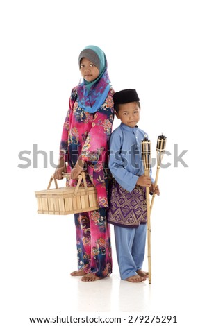 Muslim boy and muslimah girl with oil lamp during hari raya festival