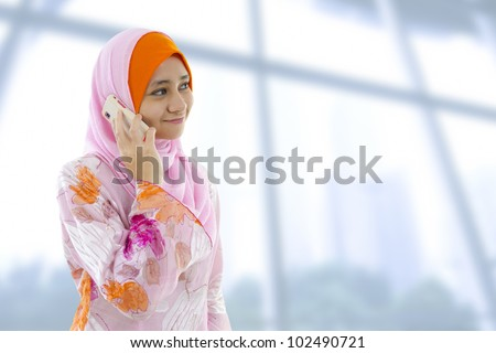 Muslim business woman on the phone, looking at side.