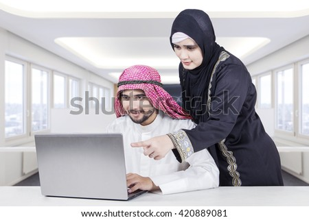 Muslim businesswoman discussing a project with her male colleague in office