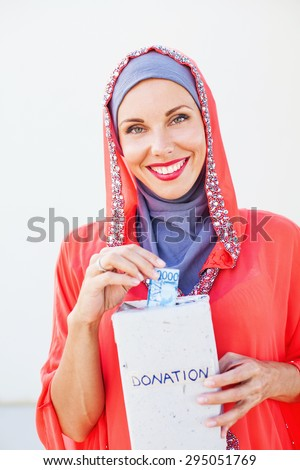 muslim caucasian woman giving alms - stock photo