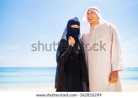 muslim couple on a beach wearing traditional dress - stock photo