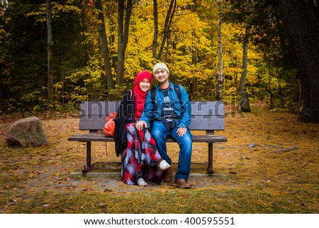 Muslim couple with colourful trees as background during autumn season