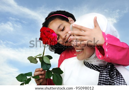 Muslim daughter giving present rose to mother - stock photo