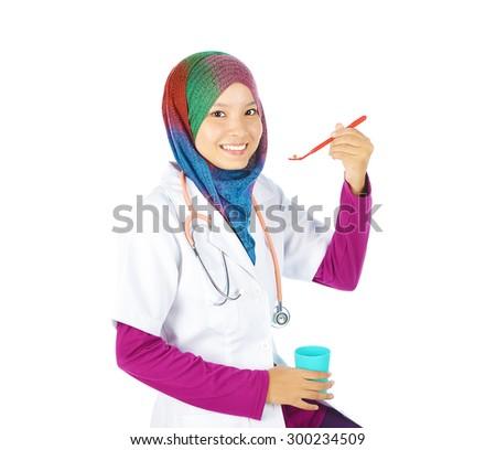 Muslim doctor taking pill using dental tool - stock photo