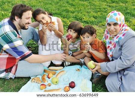 Muslim family, mother and father with three children together in nature sitting and eating on green grass: picnic - stock photo