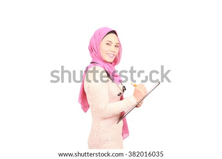 Muslim female doctor holding a clipboard - stock photo