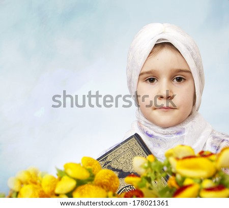 Muslim girl holding Holy Book Koran - stock photo