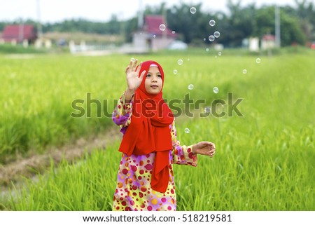 muslim girl playing bubbles at paddy field