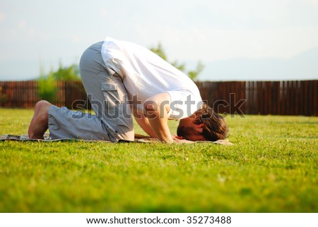 Muslim male is praying outdoor on green ground - stock photo