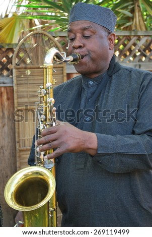 Muslim male jazz musician with his tenor saxophone outside. - stock photo