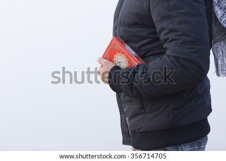 Muslim man is holding holly book Koran - stock photo
