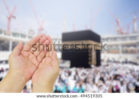 Muslim man praying at blurred background of Kaaba in Mecca