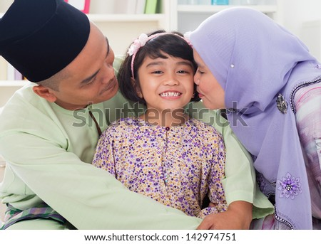 Muslim parents kissing child. Southeast Asian Malay family lifestyle. Happy smiling father mother and daughter. - stock photo