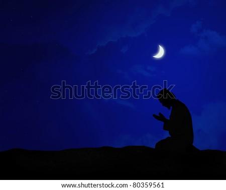 muslim praying at night under the moon - stock photo