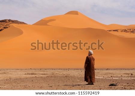 Muslim praying in the desert - stock photo